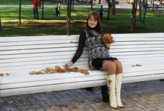 Young pregnant woman on bench with autumn leaves Royalty Free Stock Photos
