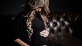 Young pregnant woman in black dress sitting half-turn in the dark room on the big brown leather sofa touching her belly. Young pregnant woman in black dress stock video