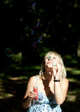 Young pregnant woman blowing soap bubbles Royalty Free Stock Photos