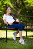 Young pregnant  woman with book sits in the park. Stock Photos