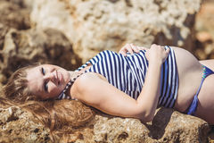 Young pregnant woman breathes the fresh sea air on a background of mountains Royalty Free Stock Photo