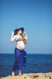 Young pregnant woman breathes the fresh sea air on a background of mountains Stock Photos