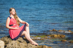 Young pregnant woman breathes the fresh sea air on a background of mountains Royalty Free Stock Photography