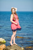 Young pregnant woman breathes the fresh sea air on a background of mountains Stock Photography