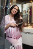 Young pregnant woman brushes hair. Stock Image
