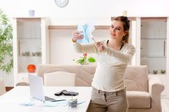 The young pregnant woman in budget planning concept. Young pregnant woman in budget planning concept stock image