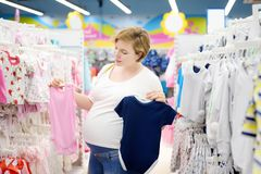 Young pregnant woman choosing pink or blue clothes in the store for newborns. Shopping for expectant mothers and baby. Pregnancy and shopping stock images