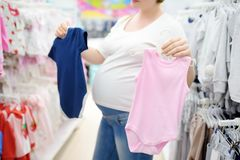 Young pregnant woman choosing pink or blue clothes in the store for newborns. Shopping for expectant mothers and baby. Pregnancy and shopping stock image