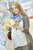 Young pregnant woman at clothes shop Stock Photos