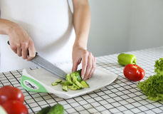 Young pregnant woman cooking vegetable salad at kitchen royalty free stock photos