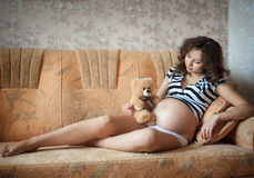 Young pregnant woman on the couch. Young pregnant woman with a teddy bear on the couch Royalty Free Stock Photos