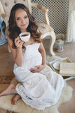 A young pregnant woman with a cup of tea. Royalty Free Stock Photography
