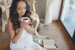 A young pregnant woman with a cup of tea. Royalty Free Stock Image