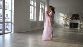 Young pregnant woman dances in light beautiful pink dress at home.  stock footage