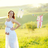 Young pregnant woman in decorated garden. Motherhood, beautiful young pregnant woman in decorated garden Royalty Free Stock Photos
