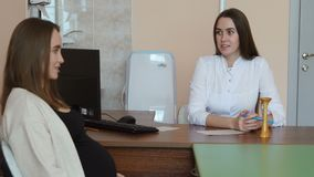 Young pregnant woman at a doctor`s reception in a white dressing gown. The doctor sitting at the table asks the patient. Questions. The perenotal center stock footage