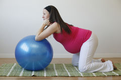 Young pregnant woman doing abdominal exercise. A young pregnant woman in a pink shirt doing an abdominal muscle exercise using a blue fitness ball Royalty Free Stock Photo