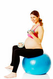 Young pregnant woman doing exercise at home Royalty Free Stock Images