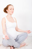 Young pregnant woman doing exersice. Beautiful young pregnant woman / teenager in white cloth in yoga pose (lotus) is meditating royalty free stock photos