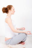 Young pregnant woman doing exersice. Beautiful young pregnant woman / teenager in white cloth in yoga pose (lotus) is meditating royalty free stock photography