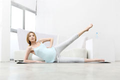 Young pregnant woman doing leg swing Stock Image