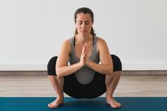 Young pregnant woman doing prenatal yoga pose with namaste hands stock photography