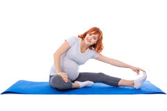 Young pregnant woman doing stretching exercises on yoga mat isol Stock Photography