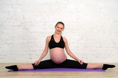 Young pregnant woman doing stretching twine exercises on yoga mat Stock Image