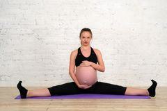 Young pregnant woman doing stretching twine exercises on yoga mat Stock Photo