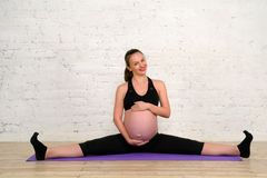 Young pregnant woman doing stretching twine exercises on yoga mat Stock Images
