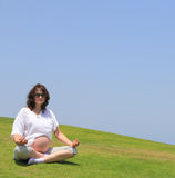 The young pregnant woman doing yoga. Happy young pregnant woman doing yoga on the lawn by the sea Royalty Free Stock Images