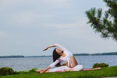 Young pregnant woman doing yoga outdoors. Beautiful young pregnant woman doing yoga in the summer park. Healthy lifestyle. River in the background Stock Image