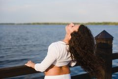 Young pregnant woman doing yoga by the river. Young pregnant woman doing yoga outdoors. Pregnant yoga. Women doing different exercises. River on background Royalty Free Stock Images
