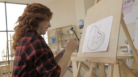 Young pregnant woman drawing painting in art studio, healthy happy lifestyle concept.  stock video footage