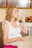 Young pregnant woman drinks water. At kitchen royalty free stock photos
