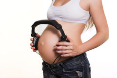 Young pregnant woman with earphones on the belly Stock Photos