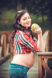 Young pregnant woman eating apple in nature Stock Photos