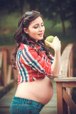 Young pregnant woman eating apple in nature Royalty Free Stock Photo