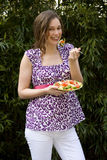 Young pregnant woman eating salad outdoors, smiling, portrait Stock Photo