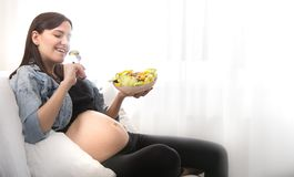 Young pregnant woman eating vegetable salad at home stock photo