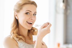 Young pregnant woman eating yoghurt. Healthy dish. Young pretty pregnant woman eating yogurt while having her healthy breakfast and sitting in a bed Stock Images