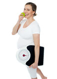 Young pregnant woman enjoy fresh green apple. And holding weighing scale in other hand hand Royalty Free Stock Photography