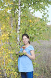 Young pregnant woman in field near birch tree Royalty Free Stock Image