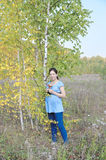 Young pregnant woman in field near birch tree Royalty Free Stock Images
