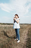 Young pregnant woman in field sniffing at the wildflowers. Selective focus Royalty Free Stock Photo
