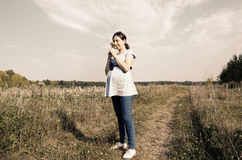Young pregnant woman in field sniffing at the wildflowers. Selective focus. Sepia toned Royalty Free Stock Images
