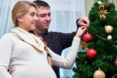 Young pregnant woman and happy father decorating christmas tree. Young pregnant women and happy father decorating christmas tree - pregnancy, holiday, family and Stock Photography