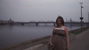 Young pregnant woman is happy in her travel destination country Latvia with a view over city Riga and river Daugava - stock footage