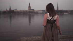 Young pregnant woman is happy in her travel destination country Latvia with a view over city Riga and river Daugava - stock video