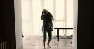Dancing pregnant woman having fun. Young pregnant woman in hat and shirt having fun and dancing in room cheerfully stock video